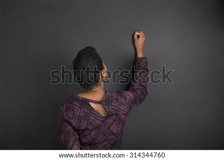 South African or African American woman teacher writing on chalk black board background inside - stock photo