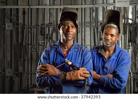 South African or American black workers or welders in factory - stock photo