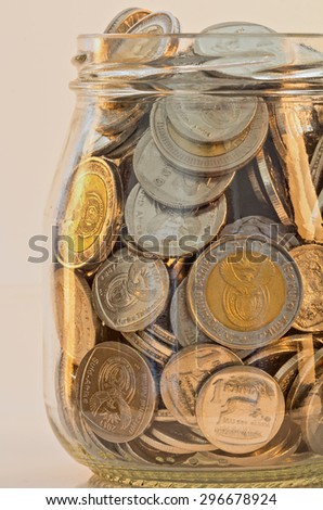 south african silver and gold minted coins in a glass jar mixed amounts of rands - stock photo