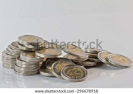 south african silver minted coins in a fallen pile against a white background - stock photo