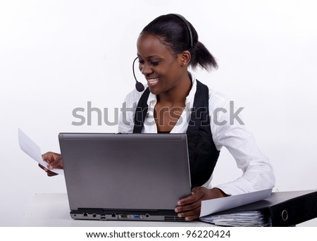 South African woman with telephone headset doing administration. - stock photo
