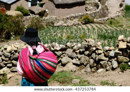 South America, Bolivia - Isla del Sol on the Titicaca lake, the largest highaltitude lake in the world. Ethnic woman returning to the village - stock photo