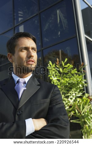South American businessman with arms crossed - stock photo