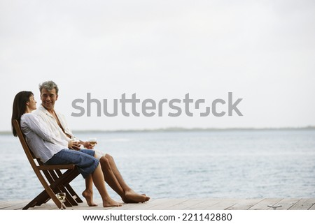 South American couple sitting on dock - stock photo