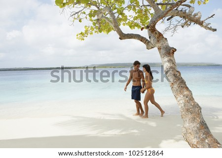 South American couple walking on beach - stock photo
