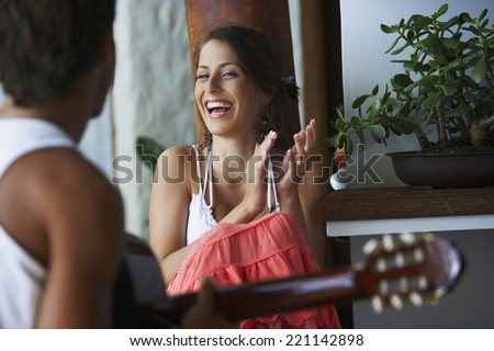 South American man playing guitar for girlfriend - stock photo