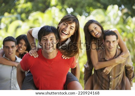 South American men giving girlfriend's piggyback rides - stock photo