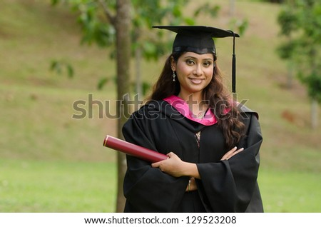 south asian female graduate with green background - stock photo