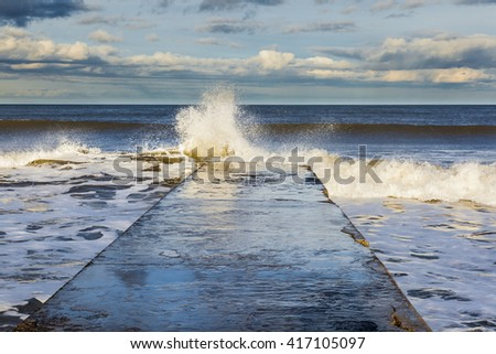 South Beach, Blyth, Northumberland.  Waves hitting the concrete jetty from the beach,