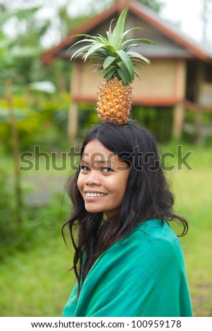 South-east asian woman with pineapple on her head - stock photo