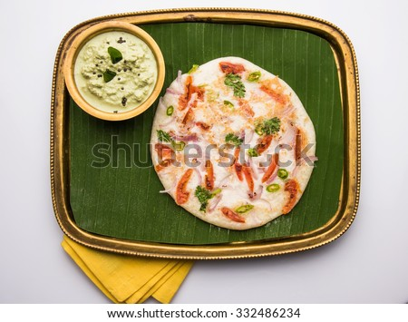 south indian food uttapam or uttappam with coconut and mint chutney on banana leaf in brass tray and bowl, front view, isolated on brown background - stock photo