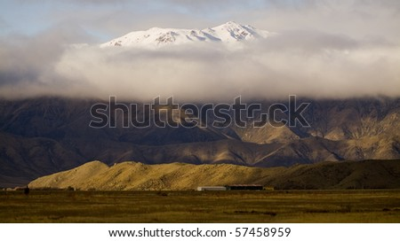 South Island, New Zealand. The tip of a mountain peaks through the clouds.