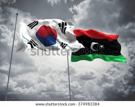 South Korea & Libya Flags are waving in the sky with dark clouds - stock photo