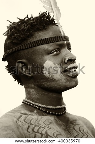 SOUTH OMO - ETHIOPIA - JULY 22, 2014: Unidentified young Mursi warrior on July 22, 2014 in South Omo, Ethiopia. A 5-year ongoing resettlement program started 2011 threatens the tribes in Ethiopia. - stock photo