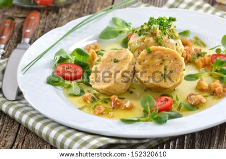 South Tyrolean bread dumplings with grey cheese, served with butter and walnuts - stock photo