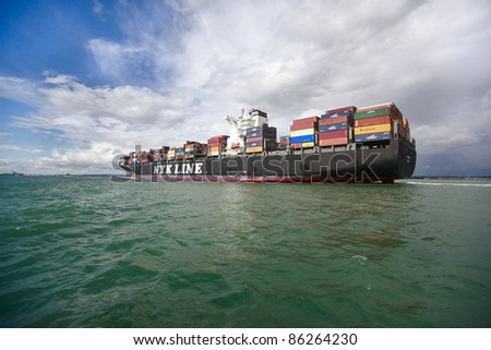 SOUTHAMPTON, UK - SEPT. 18: A loaded NYK Line container ship sails into the Port of Southampton on September 18, 2011 in Southampton, U.K. Port of Southampton is UK's busiest and most important port. - stock photo