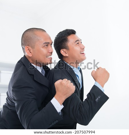 Southeast Asian businessmen celebrating success in office. - stock photo