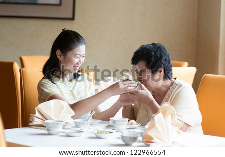 Southeast Asian Chinese family having meal in restaurant - stock photo