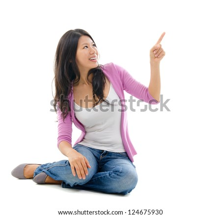 Southeast Asian Chinese woman hand pointing on blank space. Full body sitting on white background - stock photo