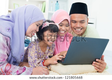 Southeast Asian family browsing internet at home. Lying on floor using computer laptop. - stock photo