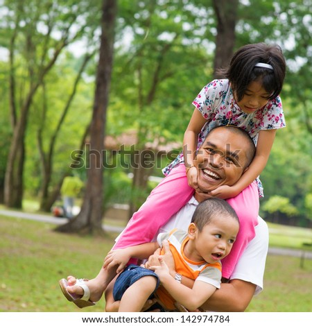 Southeast Asian family having fun at green outdoor park. Beautiful Muslim family playing together. - stock photo