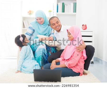 Southeast Asian family surfing internet at home. Muslim family living lifestyle  - stock photo
