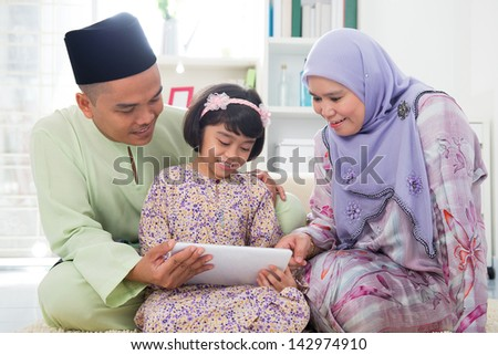 Southeast Asian family using tablet pc computer at home. Muslim family living lifestyle. Happy smiling Malay parents and child. - stock photo