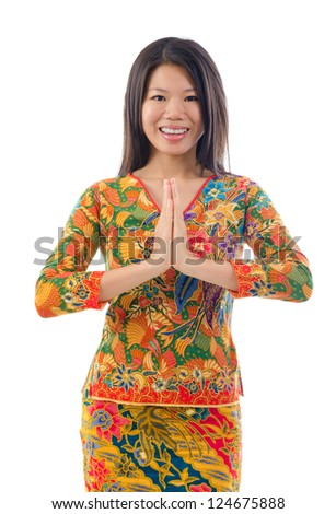 Southeast Asian female in a traditional greeting gesture, isolated white background - stock photo