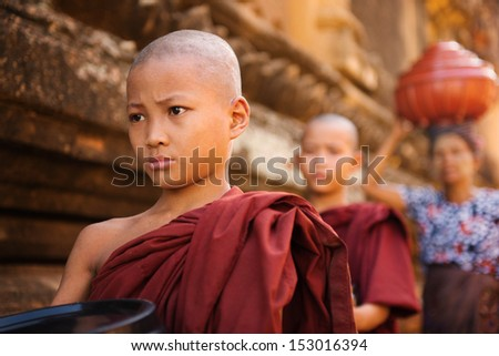 Southeast Asian young Buddhist monks walking morning alms in Old Bagan, Myanmar - stock photo