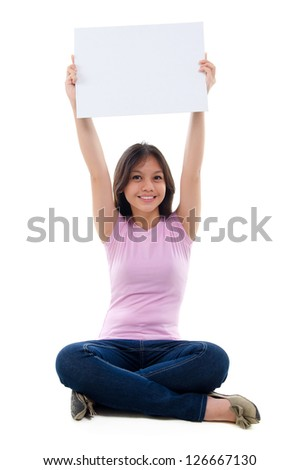 Southeast Asian young girl arms raised holding a white card board sitting over white background - stock photo
