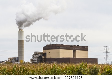 Southeast Wisconsin, USA - October 1, 2012: Electric Power Plant with Smoke Stack and Power Lines with rural corn field in foreground.