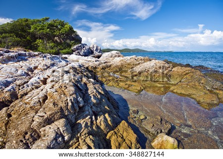 Southern Coastline wild landscape in Ko Samet island, textured stones of the coast are at foreground, Thailand - stock photo