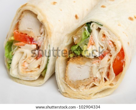Southern fried chicken wrap sandwich. Selective focus on RH wrap. - stock photo