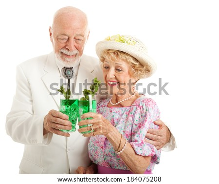 Southern senior couple enjoying traditional mint julep coctails to celebrate the Kentucky Derby.  Isolated on white.