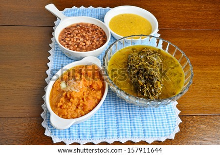 Southern style vegetables on blue gingham place mat in center of old oak dinner table waiting for the fried chicken main course. - stock photo