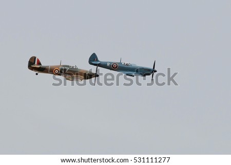SOUTHPORT, ENGLAND, SEPTEMBER 20, 2015. Vintage Supermarine Spitfire and Hawker Hurricane aircraft displaying against a grey cloud sky background at the Southport airshow