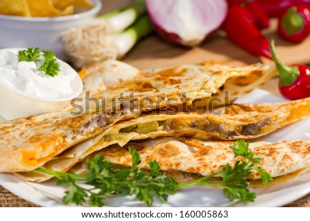 Southwest beef quesadila served with fresh chilli peppers and sourcream.