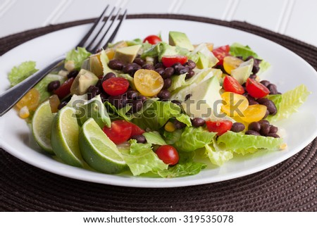 Southwest black bean, lime, cilantro, tomato, and avocado salad on a vintage antique plate macro shot - stock photo
