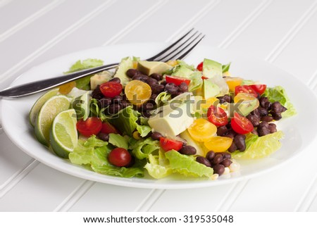 Southwest black bean, lime, cilantro, tomato, and avocado salad on a vintage antique plate side view