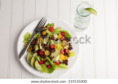 Southwest black bean, lime, cilantro, tomato, and avocado salad on a vintage antique plate - top view - stock photo