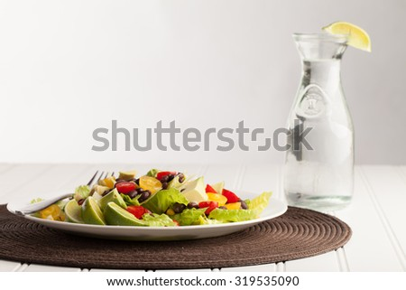 Southwest black bean, lime, cilantro, tomato, and avocado salad on a vintage antique plate with a milk jug of water - stock photo