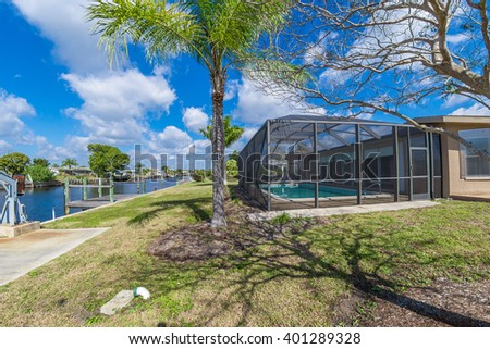 Southwest Florida homes on a canal.  View of canal home and screened cage surrounding the pool in one of the homes, boat docks and boat lift.  - stock photo