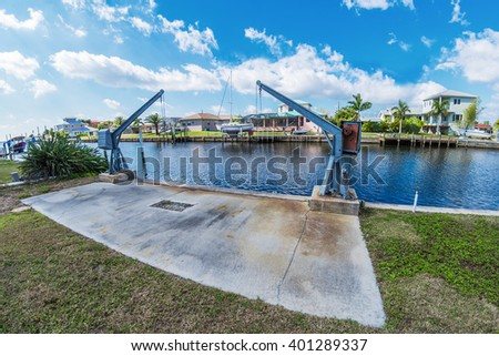Southwest Florida homes on a canal.  View of canal homes and boat lift along the sea wall on the canal.