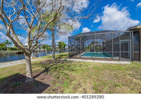 Southwest Florida homes on a canal.  View of canal homes near the screened cage surrounding the pool in one of the homes.  - stock photo
