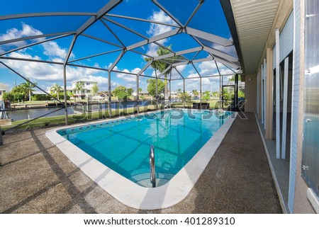 Southwest Florida homes on a canal.  View of canal homes through the screened cage surrounding the large swimming pool in one of the homes.  - stock photo