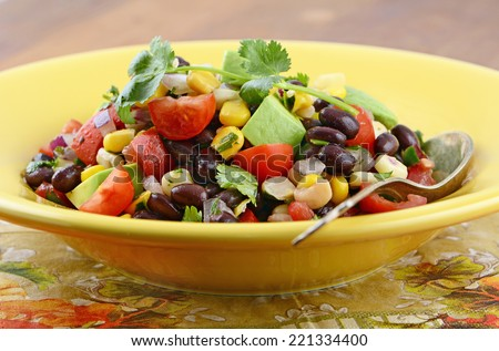 Southwestern Black bean salad with avocado, corn, tomato, red onion and cilantro in horizontal format
