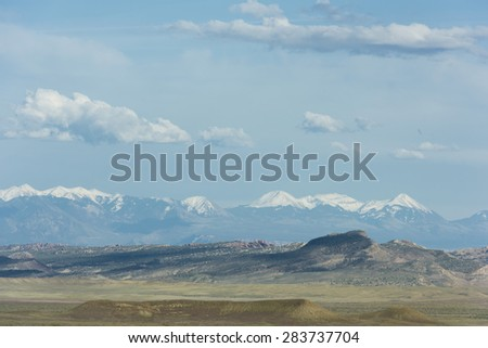 Southwestern landscape with clouds and snow capped mountains - stock photo