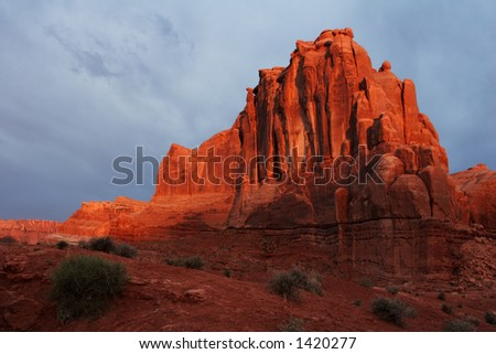 Southwestern rock-face briefly illuminated by the sunrise sun - Arches National Park, USA.