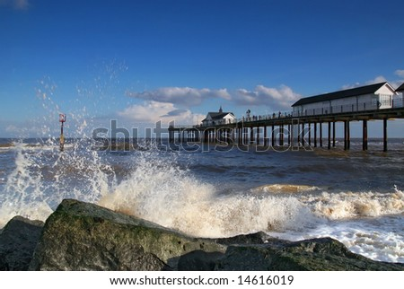 Southwold Pier in Suffolk, UK. Waves breaking on rocks with Southwold pier in the background.