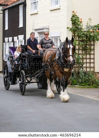 SOUTHWOLD, SUFFOLK/UK - JULY 30 : People Enjoying a Horse and Carriage Ride through Southwold Suffolk on July 30, 2016. Unidentified people